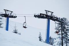 Soulevez avec les sièges rouges sur la montagne en hiver Images libres de droits