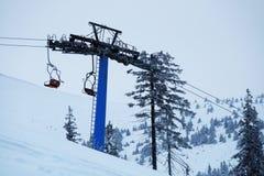 Soulevez avec les sièges rouges sur la montagne en hiver Photographie stock libre de droits