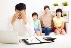 Soulignez les factures calculatrices d'homme tandis que famille s'asseyant sur le sofa image stock