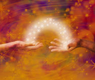 Soulmate Interaction. Man and woman both with one hand each palm up with an arc of white light and sparkles joining them on an amber colored energy formation Stock Photos