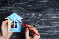 Soumettez à des peintures une maison à la couleur bleue Concept de la réparation, passe-temps, travail Réparation et peinture des photo stock
