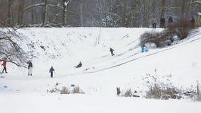 SOUMI, UKRAINE - 18 FÉVRIER 2018 : Groupe de personnes appréciant la neige et sledding en bas d'une colline Une partie des enfant clips vidéos
