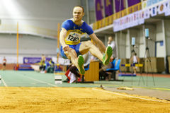 SOUMI, UKRAINE - 18 FÉVRIER 2017 : Serhiy Nykyforov exécutant son long saut dans la finale sur la voie d'intérieur ukrainienne et photo libre de droits