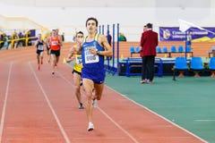 SOUMI, UKRAINE - 28 JANVIER 2018 : Yuriy Kishchenko prend la deuxième place dans la course de 3000m sur l'athlétisme d'intérieur  Photos libres de droits