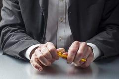 Soumis à une contrainte homme d'affaires pensant à son bureau avec le foyer sur ses mains Images stock