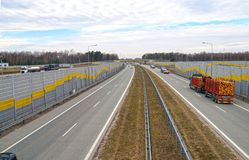 Sound-absorbing barriers reducing the noise generated by car traffic.Highway. Highway. Sound-absorbing barriers reducing the noise generated by car traffic royalty free stock image