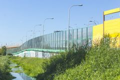 Sound-absorbing screens along the highway and the creek. Metal frames filled with glass and yellow sound-absorbing panels.Modern technology in Poland stock photo