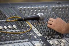 Sound adjustment. Hand on an audio mixer Stock Photos