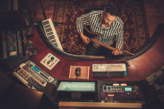 Sound engineer with guitar working in boutique recording studio. Royalty Free Stock Photo