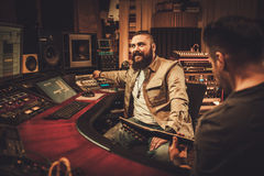 Sound engineer and guitarist recording song in boutique recording studio. Royalty Free Stock Photos