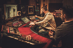 Sound engineer and guitarist recording song in boutique recording studio. royalty free stock photo