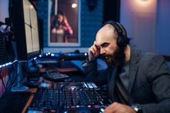 Sound engineer makes record of singer in studio. Sound engineer makes record of female singer in studio. Musician in headphones performs composition stock photos