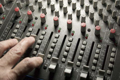 Sound Engineer on Mixing Board. Close-up of sound engineer's hand moving sliders on audio mixing board Stock Photography