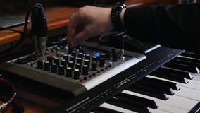 Sound engineer mixing and mastering a song on mixer board. Home studio portable mixing board. Hands turning knobs on sound mix pan. El and midi piano keyboard stock footage
