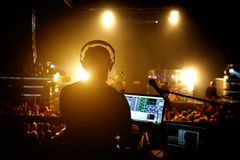 Sound engineer music producer adjusting and balancing audio on rock concert. Silhouette opposite stage light stock photo