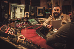 Sound engineer and musicians working in boutique recording studio. Royalty Free Stock Photography