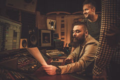 Sound engineer and musicians working in boutique recording studio. Stock Photos