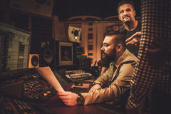 Sound engineer and musicians working in boutique recording studio. Royalty Free Stock Photo