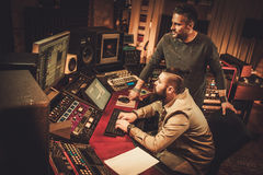 Sound engineer and musicians working in boutique recording studio. Royalty Free Stock Photos
