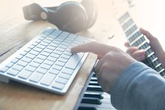 Sound engineer playing the guitar, piano and mixing some audio in a home studio. Empty copy space for Editor`s text royalty free stock image