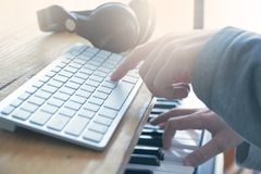 Sound engineer playing the guitar, piano and mixing some audio in a home studio. Empty copy space for Editor`s text stock photography