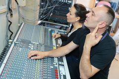 Sound engineer and producer working together in studio. Studio stock image