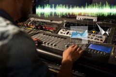 Sound engineer at recording studio mixing console. Music, technology, people and equipment concept - sound engineer with mixing console recording track at studio stock image
