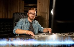 Sound engineer at recording studio mixing console. Music, technology, people and equipment concept - sound engineer with mixing console recording track at studio Royalty Free Stock Images