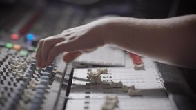 Sound engineer is reducing signals from sources and applying effects on a recorded sound in a studio. Close-up of hands stock video footage