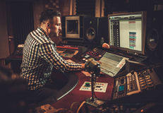 Sound engineer working in boutique recording studio. Royalty Free Stock Photo