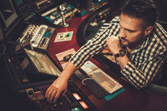 Sound engineer working in boutique recording studio. Sound engineer working in boutique recording studio Stock Photos