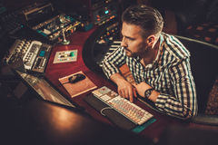 Sound engineer working in boutique recording studio. Sound engineer working in boutique recording studio Stock Images