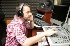 Sound engineer working on mixing console. Hispanic male sound engineer working on audio mixing console in recording studio Stock Photography