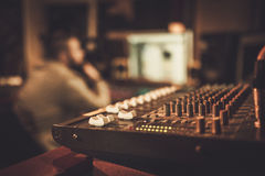 Sound engineer working at mixing panel in the boutique recording studio.  Royalty Free Stock Images