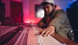 Sound engineer working on music mixer. Young man hands working on music mixer. Sound engineer mixing audio in recording studio Royalty Free Stock Photos
