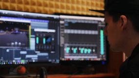 Sound engineer working at pop hit creation and producing a song at home recording studio. Mixing board and equalizer with compress. Or on blurred screen with stock footage