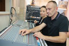Sound engineers on mixing controller. Sound Royalty Free Stock Photography