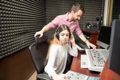 Sound engineers working in soundproof recording room Royalty Free Stock Photo