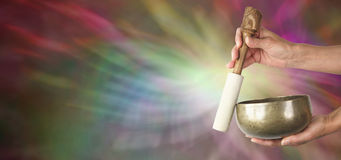 Sound Healer's web banner. Sound Healing using Tibetan Singing Bowl on wide background depicting sound waves Stock Photo