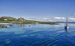 Sound of Iona. View across the sound between the islands of Iona and Mull on a sunny day in May, looking north towards Iona village and abbey with the hill, Dun Stock Photo