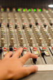 Sound mix board. Sound engineer's hand moving on sound mixing board Stock Photo