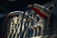 Sound mixer. Audio cable coming into analogue sound mixer in recording studio, indoor blurred shot with particular focus on center Stock Photography