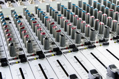 Sound mixer. Close up image of an analog audio mixing board with several channels and push buttons visible. Dials and volume levels are also visible Stock Photography