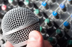 Sound mixer with microphone in hand. Part of an audio sound mixer with microphone in hand stock image