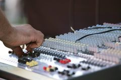 Sound mixer with operator`s hand. A sound mixer with the operator`s hand changing the potentiometer setting Stock Images