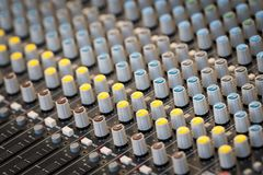 A sound mixing panel with various knobs stock photos