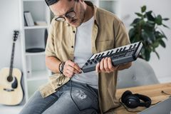 Sound producer connecting MPC pad. Young thoughtful sound producer connecting MPC pad Royalty Free Stock Photo
