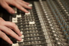 Sound producer moving faders of dirty sound mixer. Pult. focus on fingers of right hand stock photos
