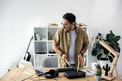 Sound producer playing on drum machine. Young sound producer playing on drum machine with drumsticks Royalty Free Stock Photo