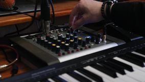 Sound producer pushes buttons and turning knobs on mixing board with equalizer and compressor. Sound engineer creating music at ho. Me recording studio. Music stock video footage